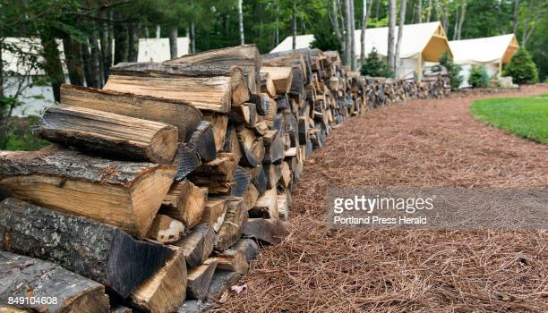 Firewood is artfully stacked and ready for guests' use at a communal firepit within Sandy Pines Campground in Kennebunkport