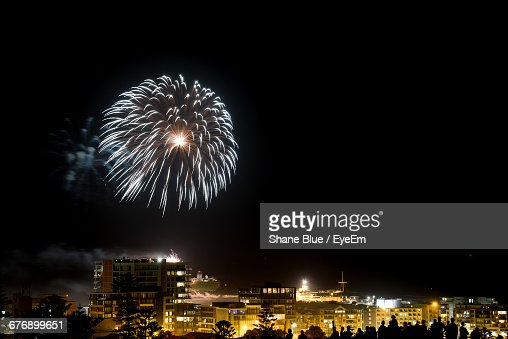 Firework Display Over Illuminated City At Night