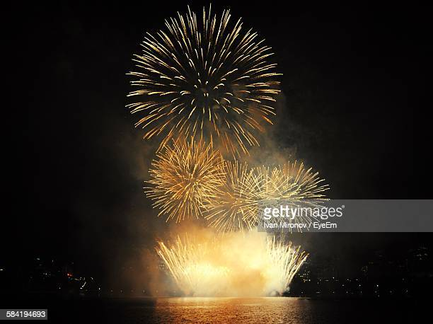 Firework Exploding Over River Against Sky At Night