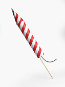 Red and white striped firework rocket isolated on white background. Vertical composition with copy space. Clipping path is included.