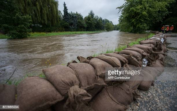 Fireworkers stand next to sandbags at the bank of the river Innerste during rainfall on July 26 2017 in Hildesheim northern Germany Ongoing rain led...