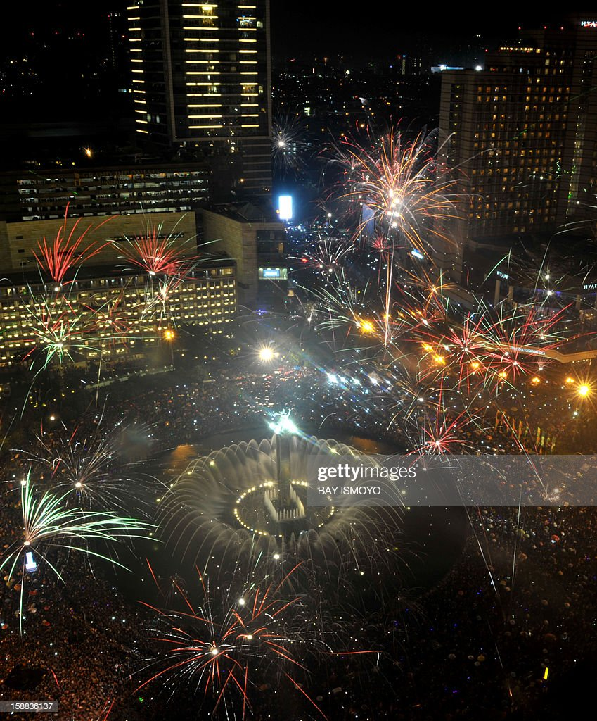 Fireworks are launched over Jakarta's main business road to mark the new year in Jakarta on January 1, 2013 . AFP PHOTO / Bay ISMOYO