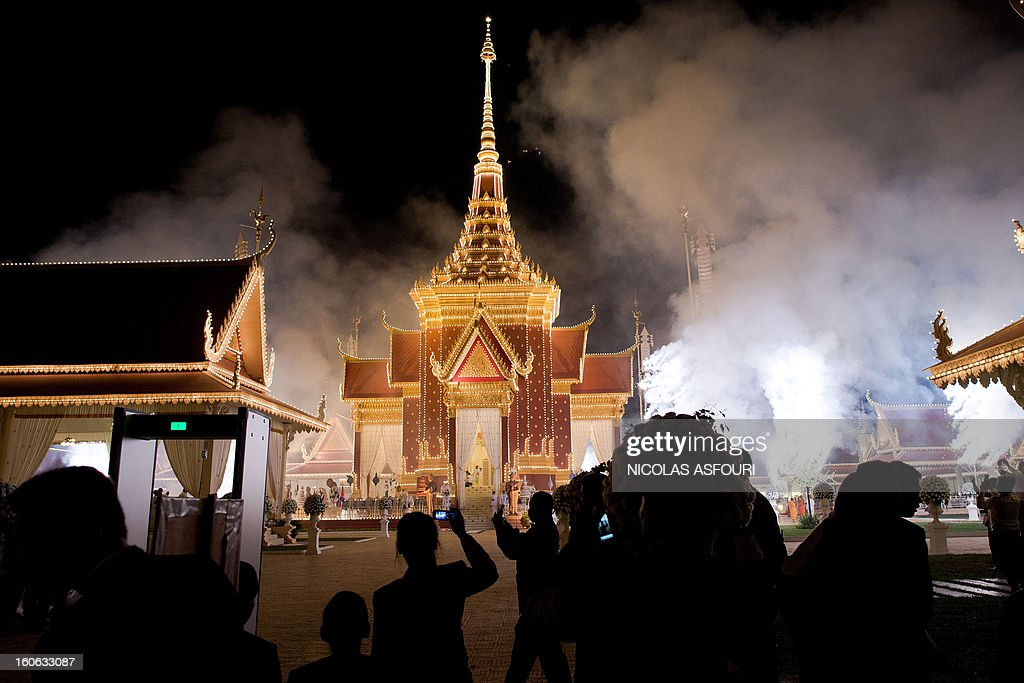Fireworks are lit at the crematorium to mark the beginning of the cremation where a coffin bearing the remains of Cambodia's late King Norodom Sihanouk is placed, near the Royal Palace in Phnom Penh on February 4, 2013. Thousands of mourners massed in the Cambodian capital as the kingdom cremated its revered former King Norodom Sihanouk, who steered his country through six turbulent decades. AFP PHOTO/ Nicolas ASFOURI