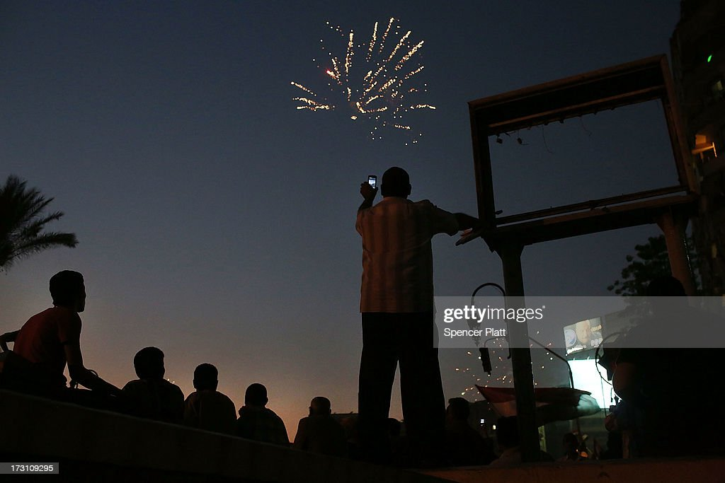 Fireworks are viewed as tens of thousands of people attend a rally in Tahrir Square against ousted Egyptian President Mohamed Morsi on July 7 2013 in...