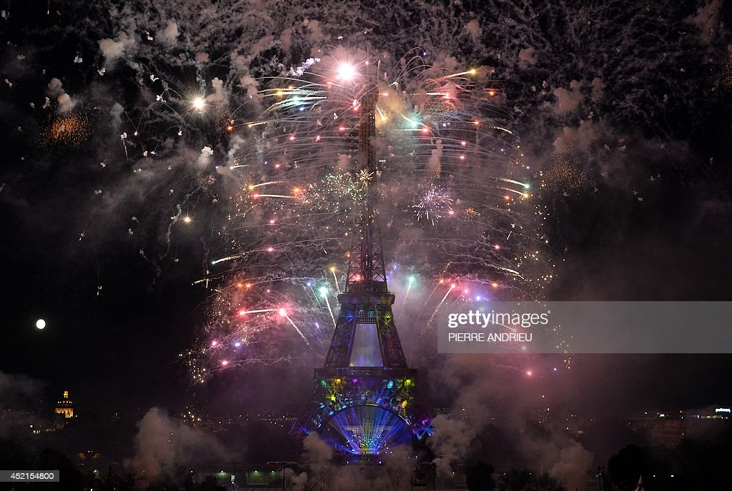 Fireworks burst around the Eiffel Tower in Paris on July 14 2014 as part of France's annual Bastille Day celebrations AFP PHOTO / PIERRE ANDRIEU