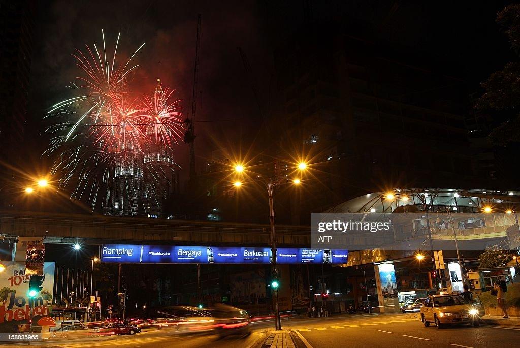 Fireworks burst in the sky near Malaysia's landmark Petronas Twin Towers during the New Year celebrations in Kuala Lumpur on January 1, 2013.