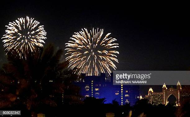 Fireworks burst over the Atlantis Hotel at the manmade Palm Island in Dubai on January 1 2016 A spectacular fireworks display lit up the sky above...