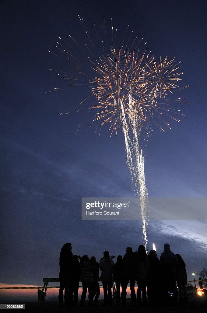 A fireworks display at sunset lit up the sky over Long Island Sound after the new playground opening ceremony, Dec. 11, 2013, in Bridgeport, Conn., the latest playground in the Sandy Ground project, this one dedicated to Josephine Gay, one of the 20 children killed one year ago at the Sandy Hook Elementary School.