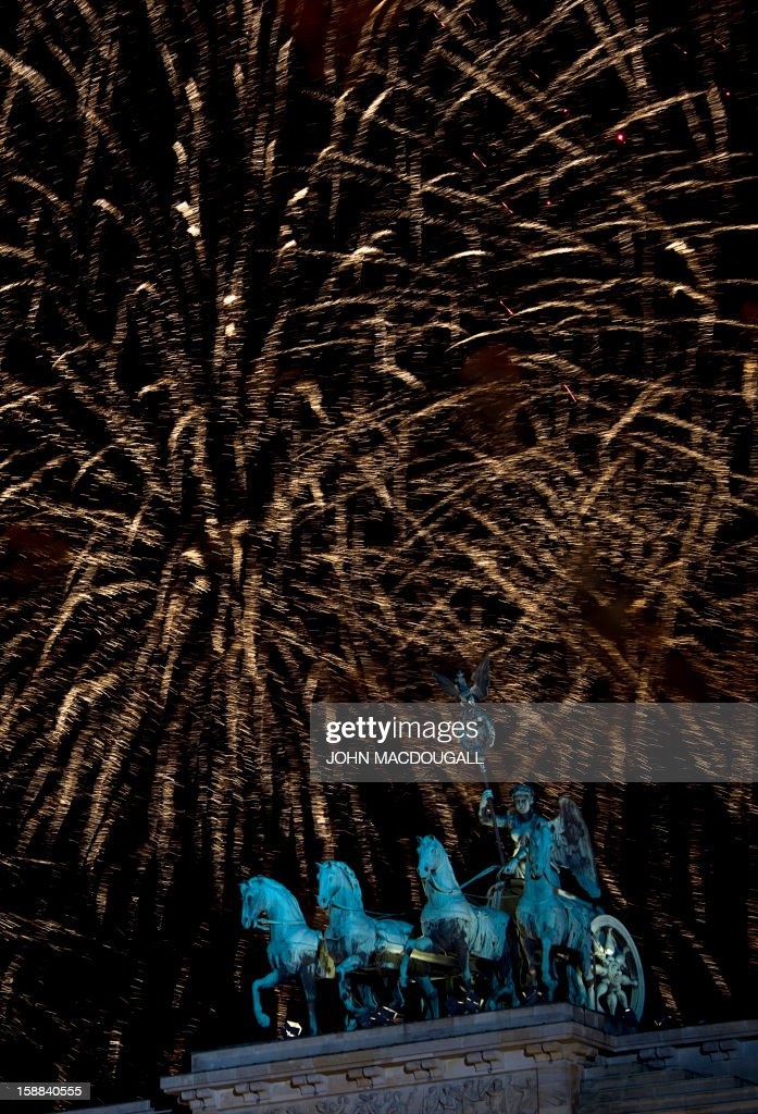Fireworks erupt over the Brandenburg Gate on January 1, 2013 in Berlin as part of the New Year's celebrations. MACDOUGALL