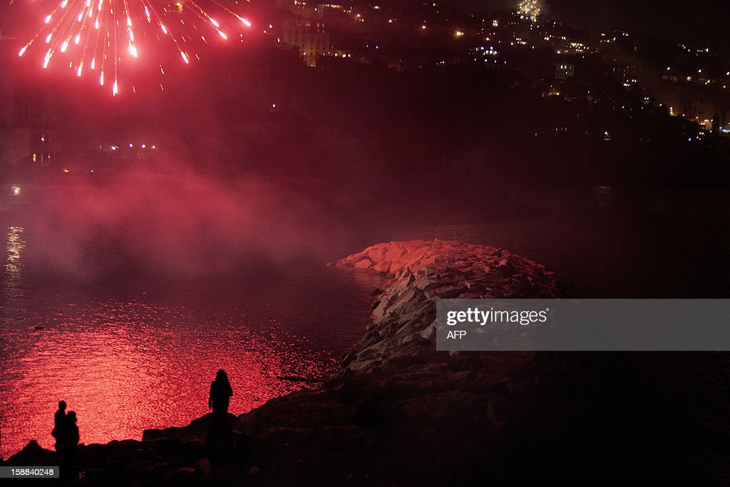 Fireworks erupt over the Naples skyline in southern Italy on January 1, 2013 to mark New Year's celebrations. World cities from Sydney to Dubai rang in the New Year with a spectacular global wave of firework displays. AFP PHOTO / Machi Jones
