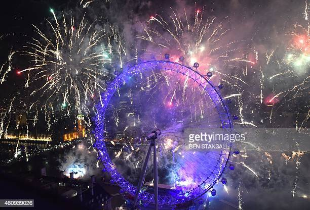 Fireworks explode above the Houses of Parliament and the London Eye during the New Year celebrations in central London just after midnight on January...