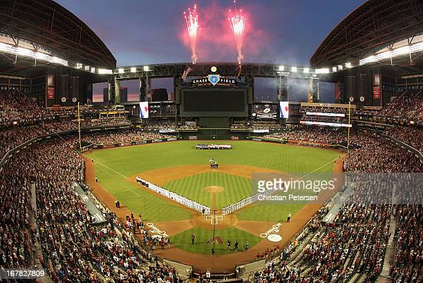 Fireworks explode as the St Louis Cardinals and the Arizona Diamondbacks stand attended for the National Anthem before the MLB Opening Day game at...