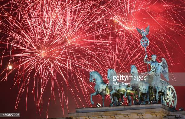 Fireworks explode behind the Quadriga statue on top of the Brandenburg Gate shortly after midnight on January 1 2014 in Berlin Germany Tens of...