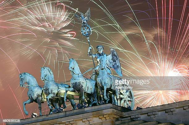 Fireworks explode behind the Quadriga statue on top of the Brandenburg Gate shortly after midnight on January 1 2015 in Berlin Germany Tens of...