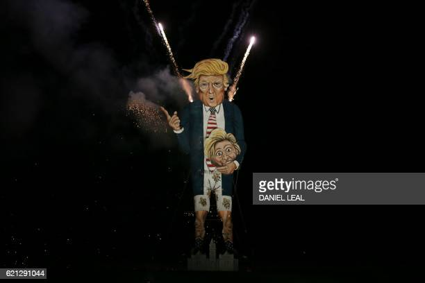 Fireworks explode out of the back of an effigy of US presidential candidate Donald Trump while it is burned as the 'Celebrity Guy' at the Edenbridge...