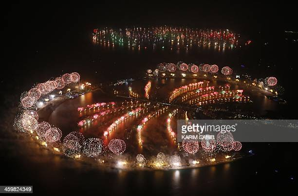 Fireworks explode over Palm Jumeirah in Dubai on January 1 2014 to celebrate the new year Dubai kicked off New Year with a dazzling bid for a new...