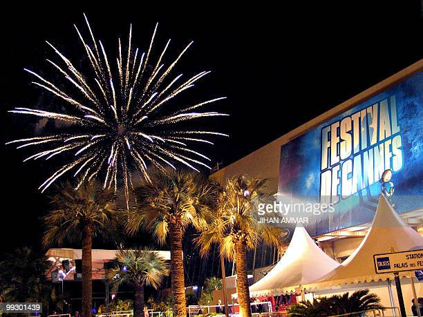 Fireworks explode over the film festival palace in Cannes late 22 May 2004 at the end of the 57th Cannes Film Festival in the French Riviera town US...
