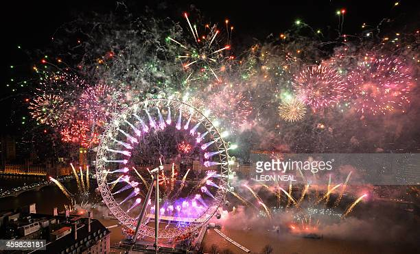 Fireworks explode over the London Eye and the Houses of Parliament along the river Thames during the New Year celebrations in central London just...