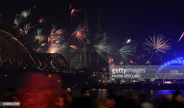Fireworks explode over the river Rhine as in background can be seen the Cologne Cathedral during a New Year's party in Cologne western Germany on...