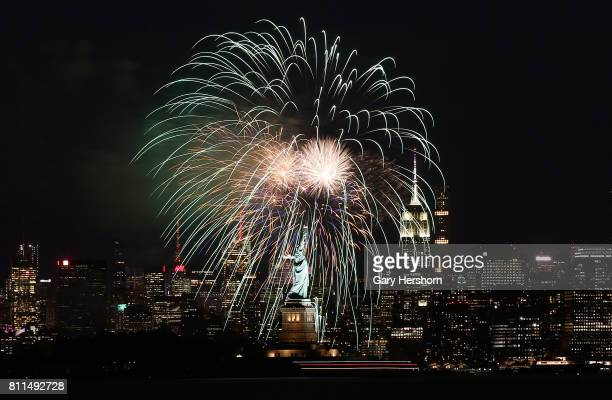 Fireworks explode over the Statue of Liberty and in front of the Empire State Building in New York City on July 6 2017 as seen from Bayonne New Jersey