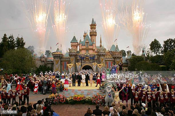 Fireworks explode under cloudy skies as Disney dignitaries and characters appear in front of Sleeping Beauty Castle at the close of ceremonies for...