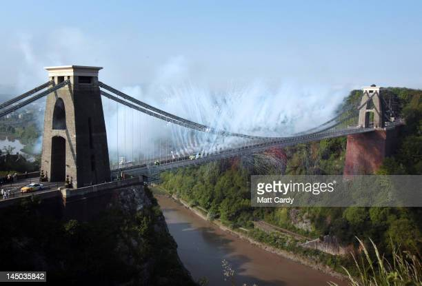Fireworks greet an Olympic torchbearer as they run with Olympic flame across the Clifton Suspension Bridge on May 23 2012 in Bristol England The...