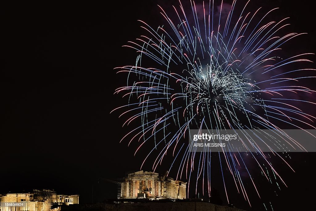 Fireworks illuminate the ancient temple of Parthenon atop the Acropolis hill during the new year's celebrations in Athens on January 1, 2013. AFP PHOTO / ARIS MESSINIS