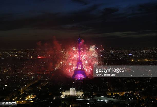 Fireworks illuminate the night sky around the Eiffel Tower in the French capital Paris on July 14 2017 as part of France's annual Bastille Day...