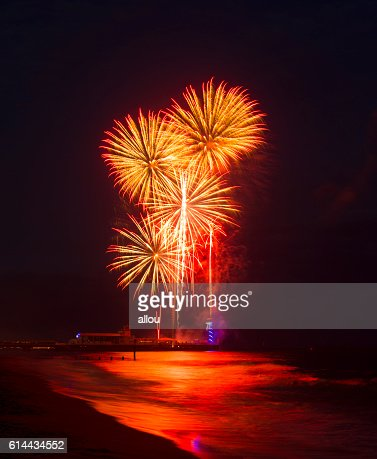 Fireworks in the sky reflected in seas at Bournemouth Pier : Stock Photo