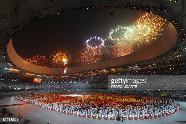 Fireworks light the sky as the Olympic flame burns during the opening ceremony of the 2008 Beijing Olympic Games in Beijing on August 8 2008 The...