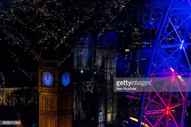 Fireworks light up Big Ben and the London Eye just after midnight on January 01 2016 in London England Thousands of people lined the banks of the...