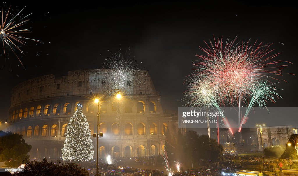Fireworks light up the ancient Colisseum in central Rome's via dei Fori just after midnight on January 1, 2013. World cities from Sydney to Dubai rang in the New Year with a spectacular global wave of firework displays. AFP PHOTO / VINCENZO PINTO