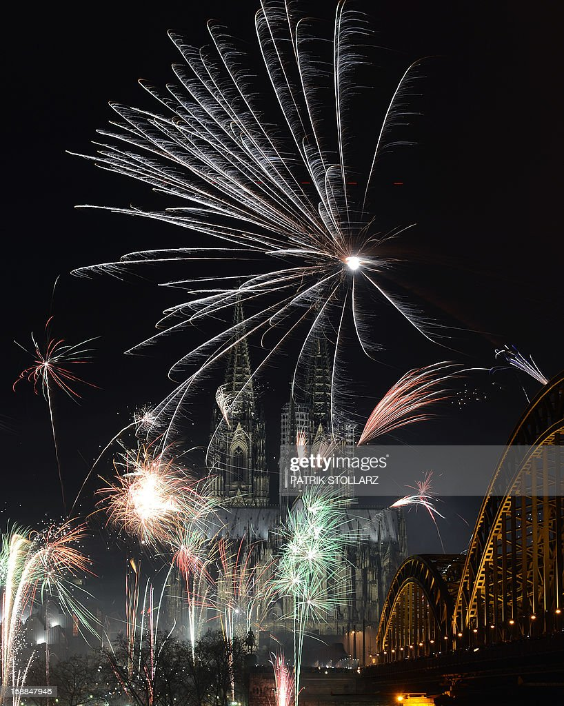 Fireworks light up the Dom church on the Rhine river in Cologne , western Germany just after midnight on January 1, 2013. AFP PHOTO / PATRIK STOLLARZ