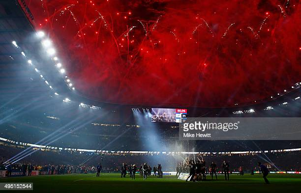 Fireworks light up the sky as New Zealand players celebrate on the pitch after victory in the 2015 Rugby World Cup Final match between New Zealand...