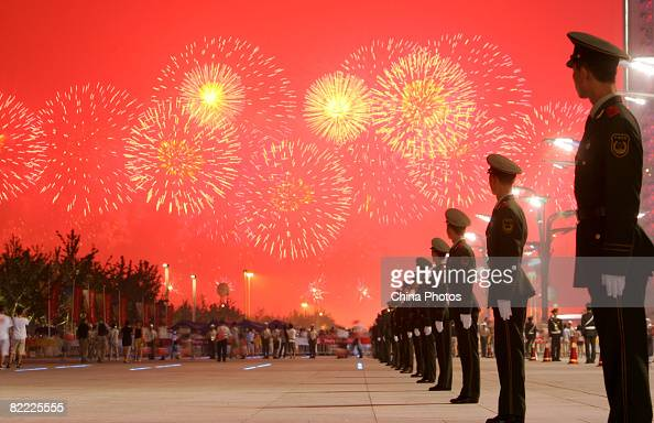 Fireworks light up the sky as paramilitary policemen stand guard during the Opening Ceremony for the Beijing 2008 Olympic Games on August 8 2008 in...