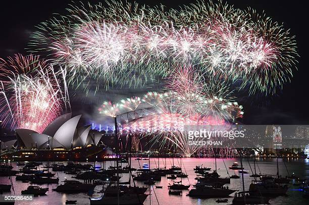 Fireworks light up the sky over Sydney's Opera House and Harbour Bridge during New Year celebrations in Sydney on January 1 2016 / AFP / SAEED KHAN