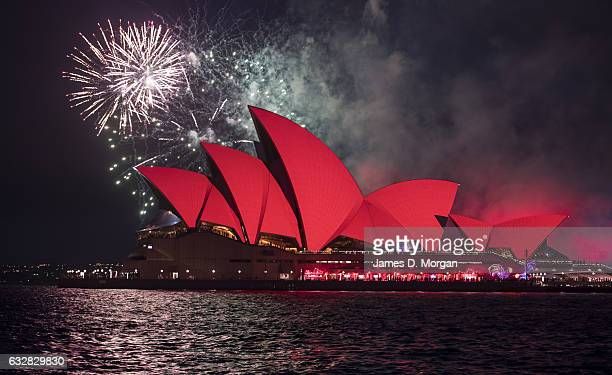 Fireworks light up the skyline over the Sydney Opera House lit with red floodlights on January 27 2017 in Sydney Australia A number of events are...