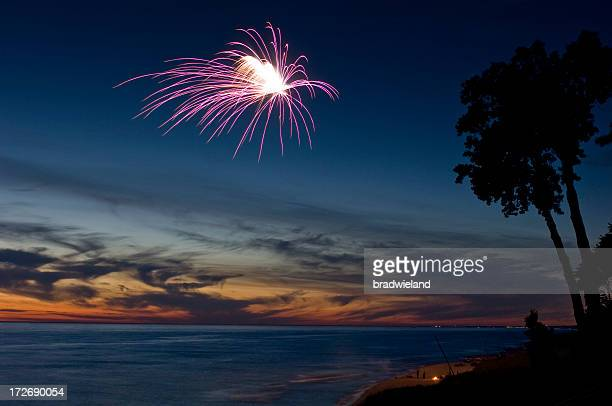 Fireworks on a beach at sunset