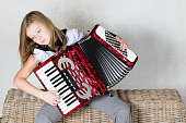 A girl focusing on playing an accordion