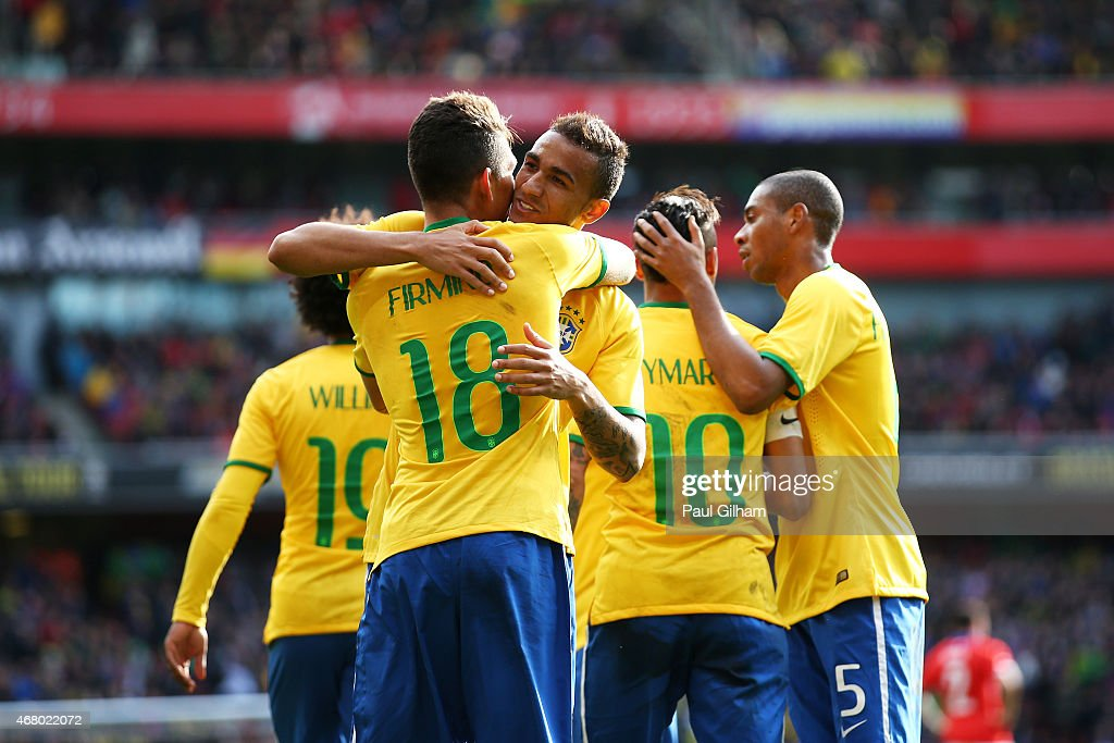 Firmino of Brazil is congratulated by teammates after scoring the opening goal during the international friendly match between Brazil and Chile at...