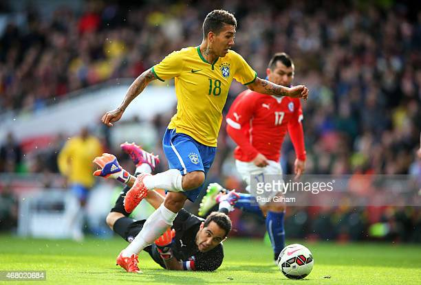 Firmino of Brazil rounds goalkeeper Claudio Bravo of Chile to score the opening goal during the international friendly match between Brazil and Chile...