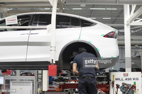 A firmware installation notification sign sits on a window of a Tesla Model X sports utility vehicle as an employee fits a rear axle during assembly...