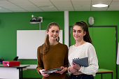 Two teenage girls standing together in a classroom with school eqipment in their hands.