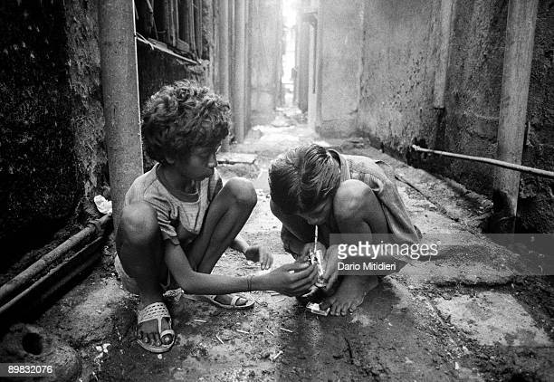 Firoze and Sadik smoke brown sugar in an alleyway in the Red Light district of Kamatipura