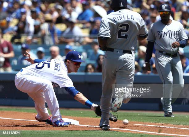 Firsbaseman Cody Bellinger of the Los Angeles Dodgers can't handle a throw to first base during the first inning of the MLB game against the San...