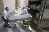 First 10 coffins with bodies of migrants who died in an abandoned lorry are unloaded from a van on August 28 2015 for an investigation at a forensics...