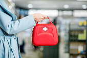 Woman holding red first aid kit at the farmacy store