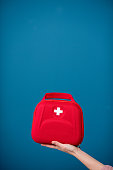 Holding first aid kit on the blue background