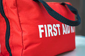 A red first aid kit bag with a black zip and handle, in closeup.