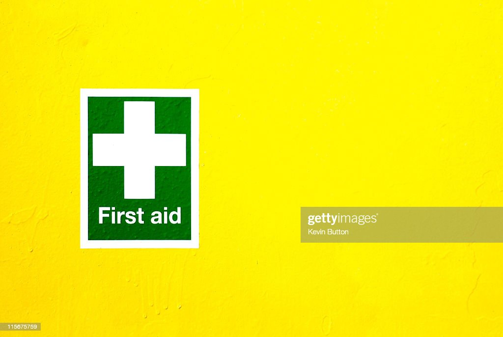 First Aid Sign on Yellow : Stock Photo